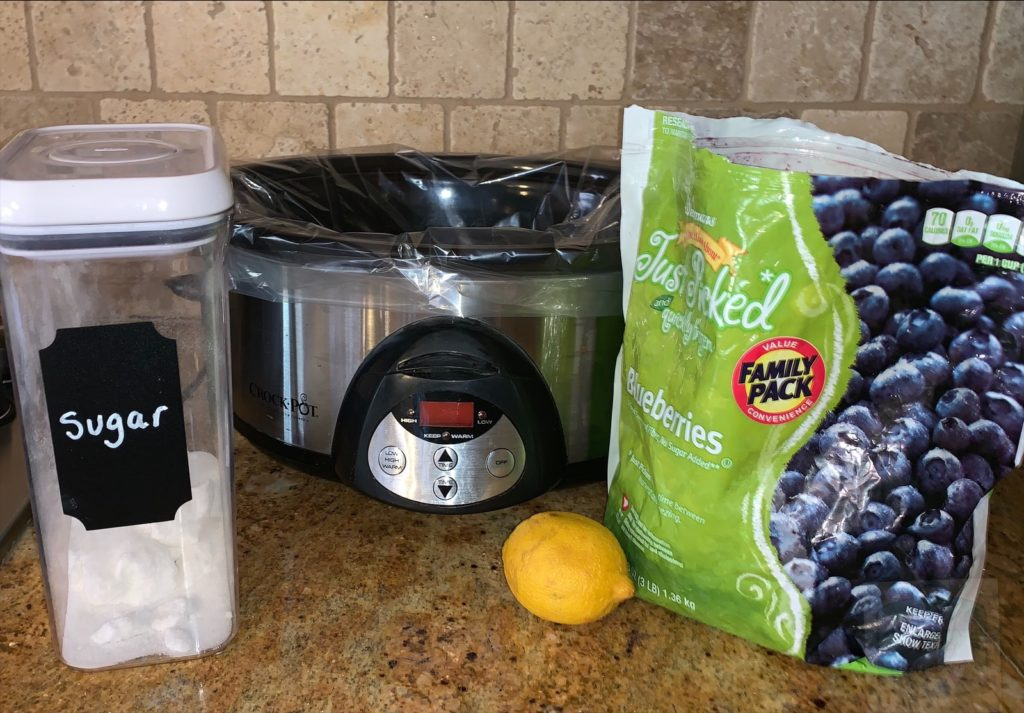 A bag of frozen blueberries, a lemon and a container of sugar on a counter in front of a slow cooker