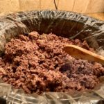 A slow cooker full of browned ground beef being stirred with a wooden spoon