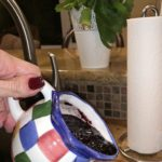 blueberry sauce being poured out of a small pitcher