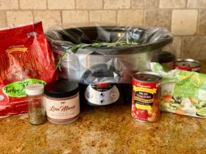 Picture of crockpot with various ingredients around it in their original packaging