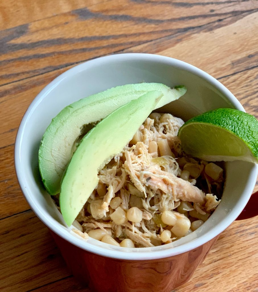 chicken and corn chili with avocado slices and a lime wedge in a red cup