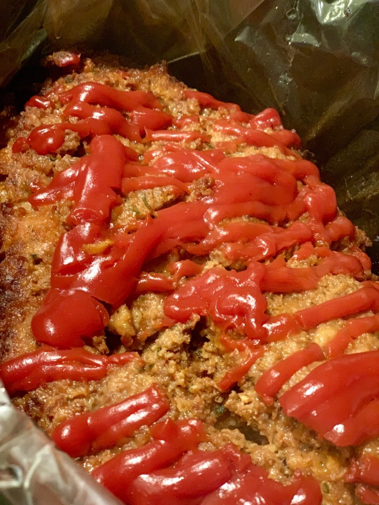 a close up shot of an oval shaped meatloaf with ketchup on top.