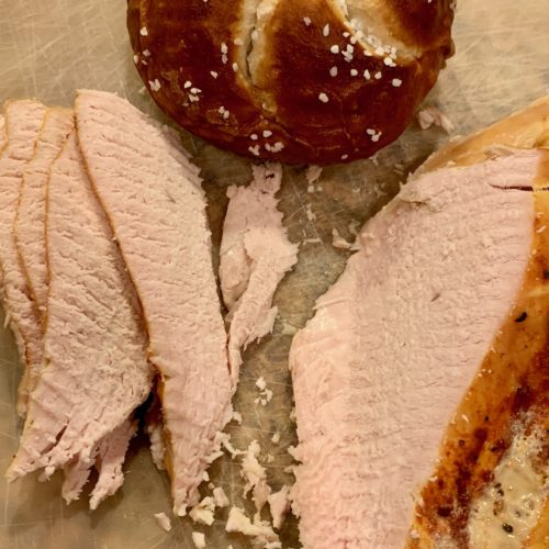 easy slow-cooker roasted turkey breast shown partially sliced with a pretzel roll
