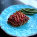 Square piece of slow cooker meatloaf topped with sauce and green beans in the background