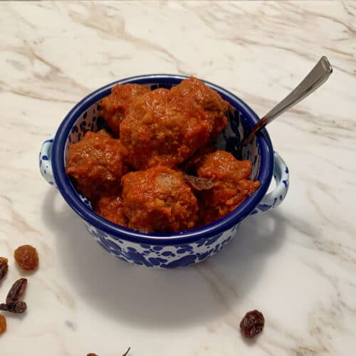 Meatballs in a bowl with a blue rim with a spoon sticking out