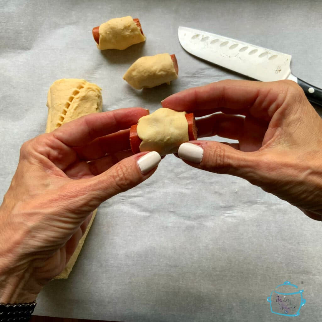 two hands holding a piece of hot dog wrapped in crescent roll