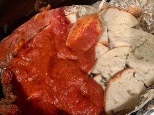 Pizza sauce being spooned over cut up bagels