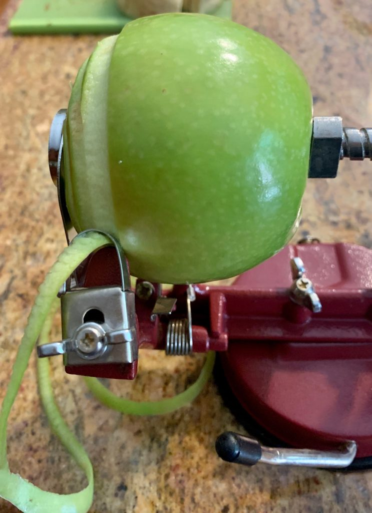 Apple half peeled on peeler