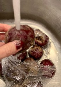 raw beets under running water in a sink