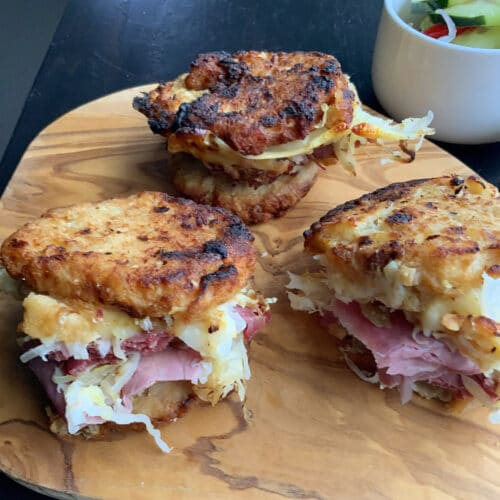 Potato pancake grilled Reuben sandwich on a wooden board with a salad in the background