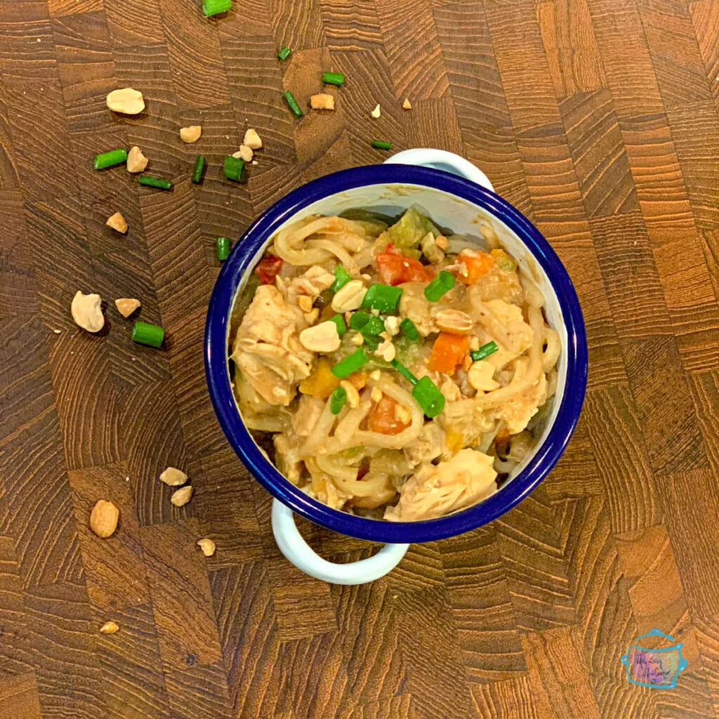 Looking down on a bowl of noodles and chicken topped with peanuts