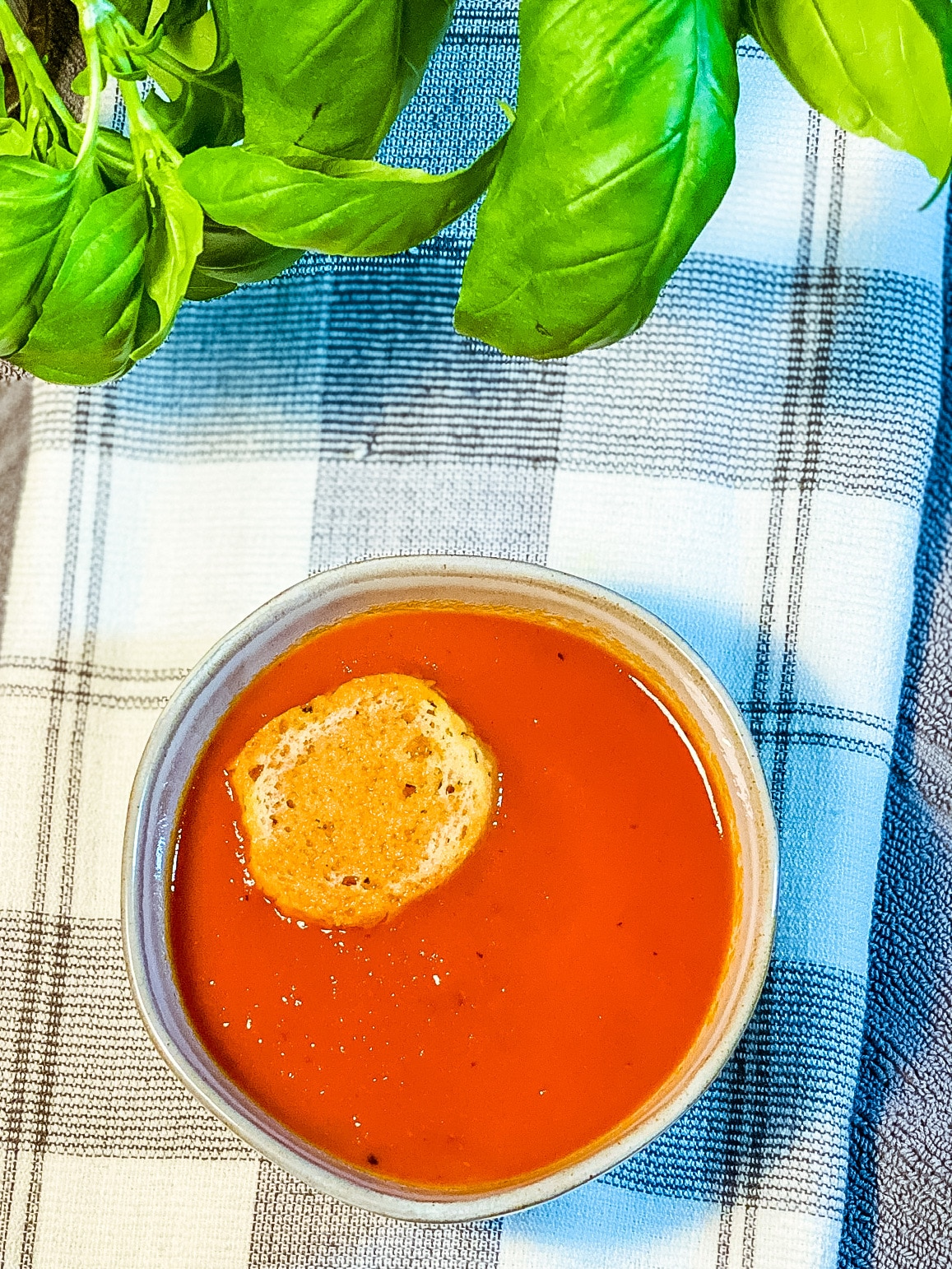slow cooker tomato soup with a large crouton floating in it