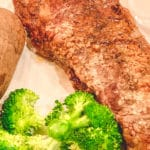 Cooked steak on a white plate served with Broccoli and a potato