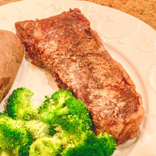 Steak on a white plate with garlic, broccoli.