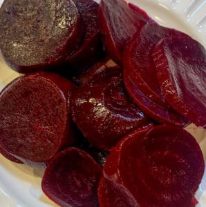 Roasted beets sliced on a white plate