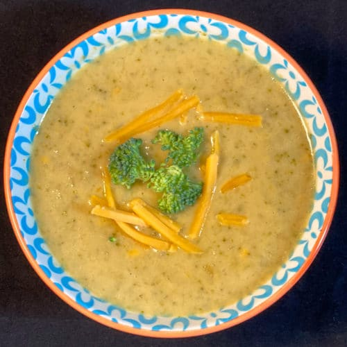 Top down view of bowl of broccoli cheddar soup with fresh broccoli and cheese shreds floating on top