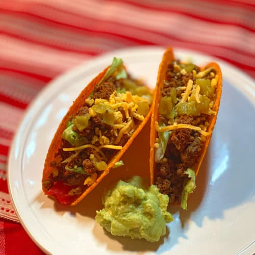 Photo of two hard shelled tacos filled with ground beef, green chili peppers and shredded cheese