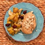 top view of a cooked chicken breast topped with feta cheese, kalamata olive and greek veggies