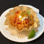 Side view of shredded chicken in a taco shell topped with sour cream, shredded cheese and salsa