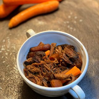 Shredded roast and carrots in a bowl with raw carrots in the background