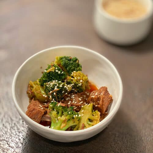 Broccoli, beef and sesame seed in a round white bowl