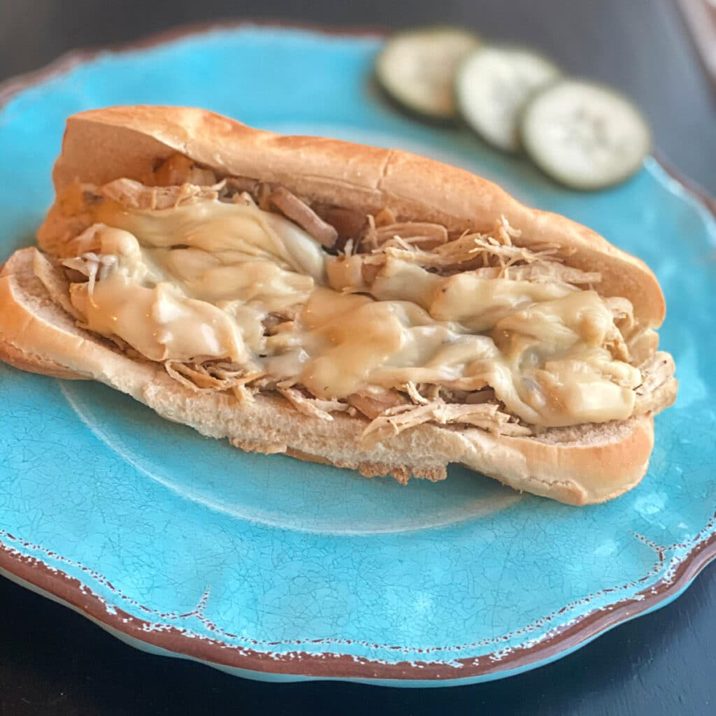 close up of hoagie roll, chicken mixture and melted cheese