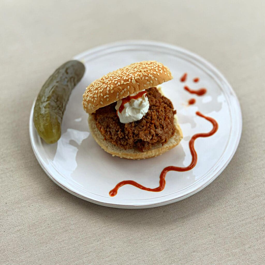 close up of seasoned beef on a round sesame bun topped with sour cream and decorated with hot sauce