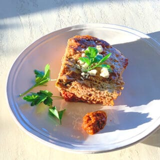 Corner piece of meatloaf on a round white plate in the afternoon sun