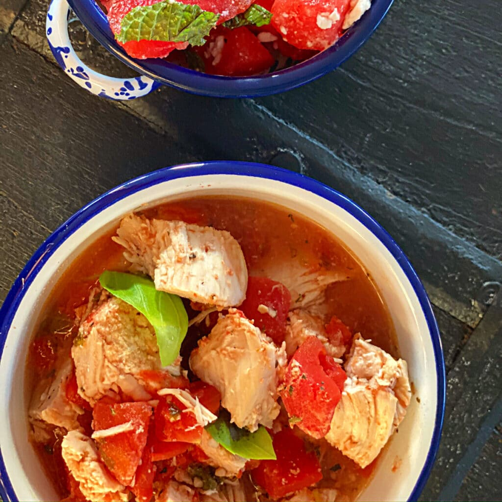 top view of chicken with tomato and basil in a round bowl with watermelon salad in background