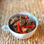finished Mongolian Beef in a round white bowl with handles on a wicker mat