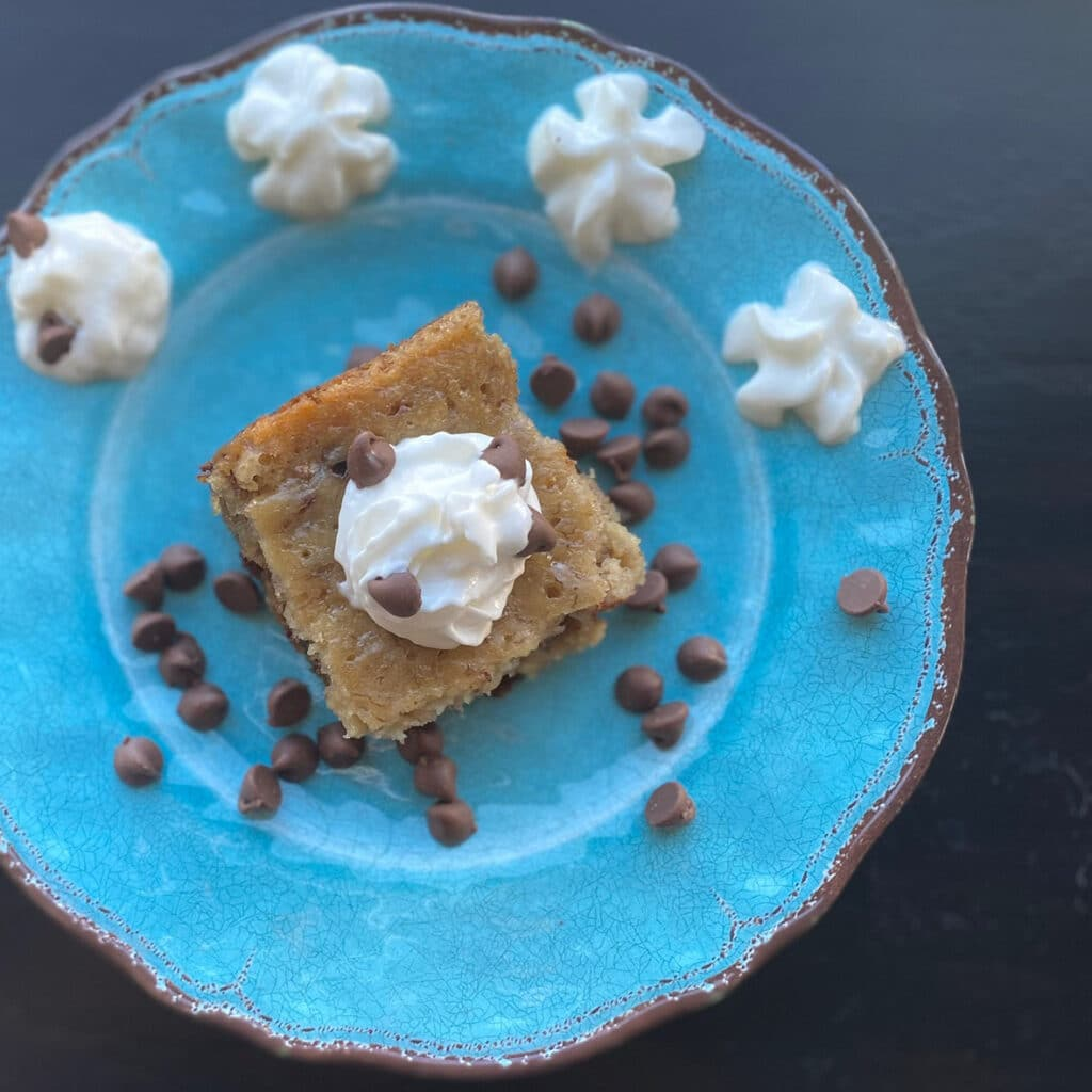 top view of brownie brownies on a blue plate with chocolate chips sprinkled around a dollop of whipped topping