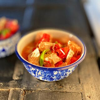 a bowl of finished tomato basil chicken with a blue rim