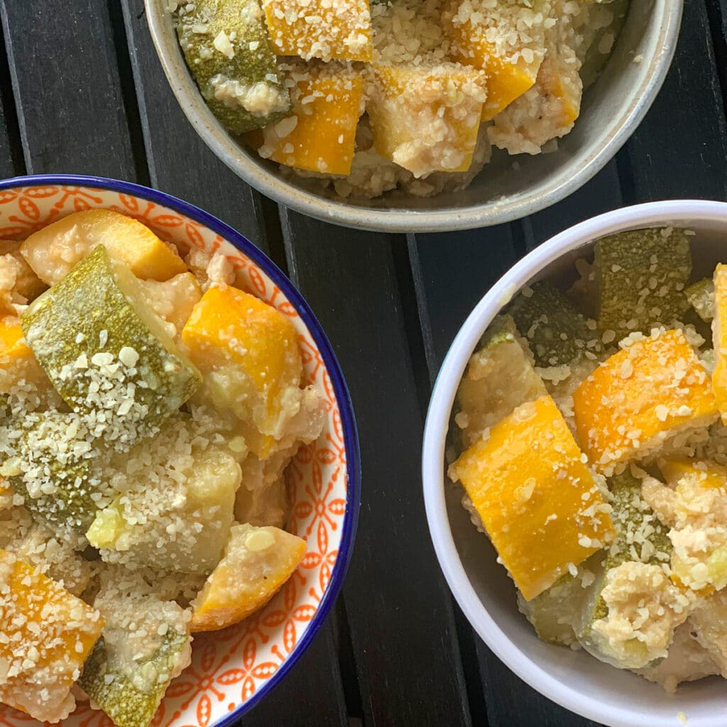 Three bowls filled with yellow and green veggies coated in grated parmesan cheese