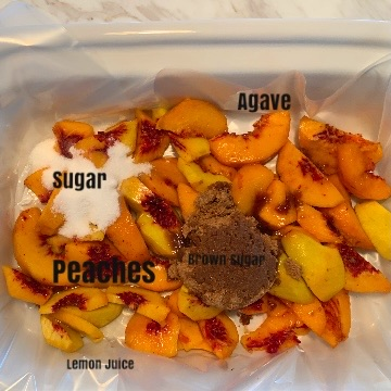 small shot of sliced peaches in slow cooker with each ingredient for bottom layer labeled