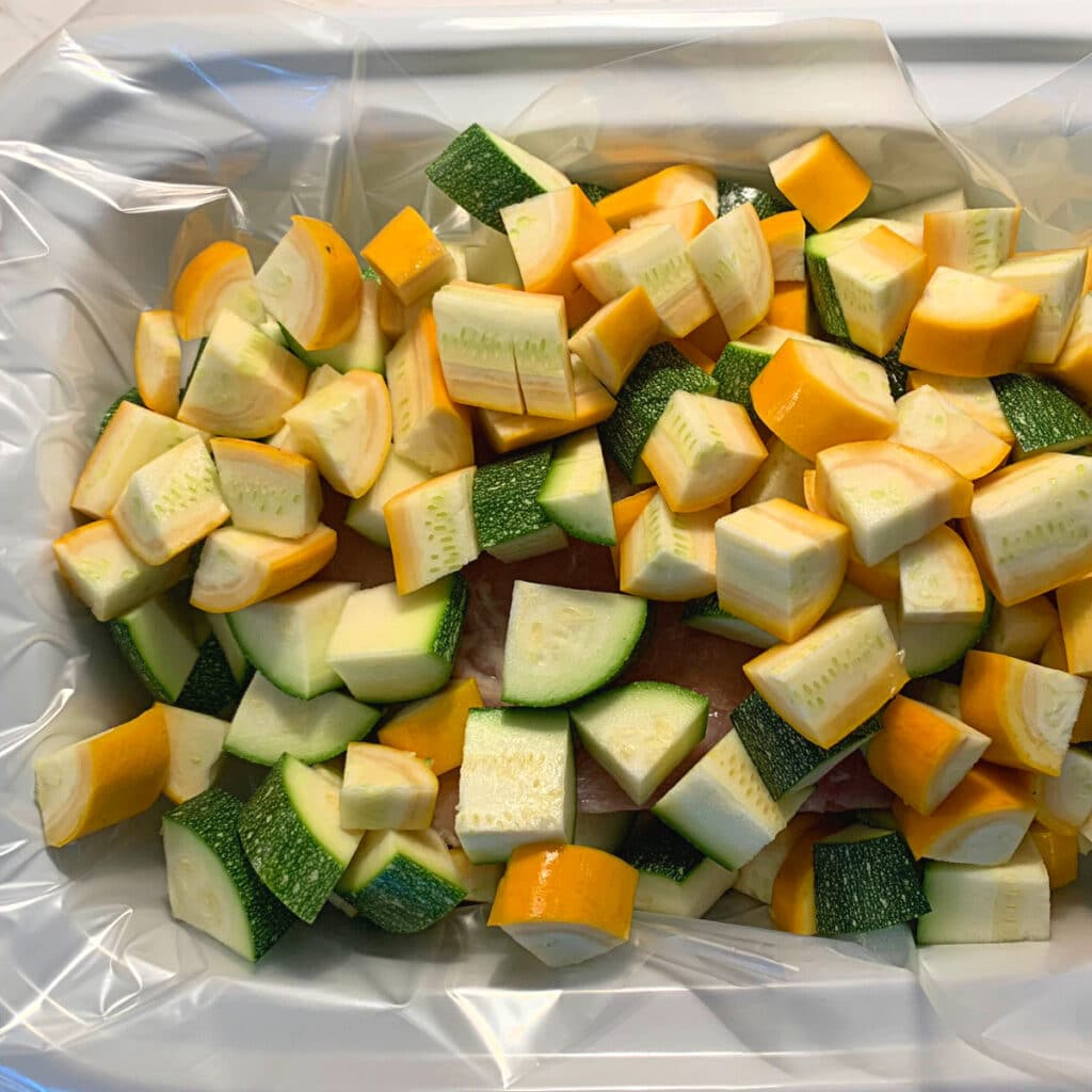 Summer squash and zucchini cut in chunks in a white slow cooker