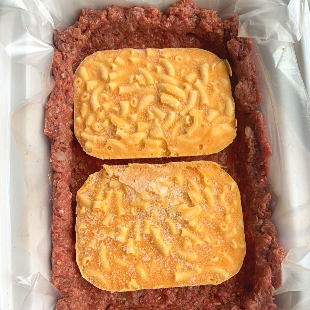 meatloaf in pan on bottom and up walls of slow cooker with two small frozen mac and cheese blocks in the middle