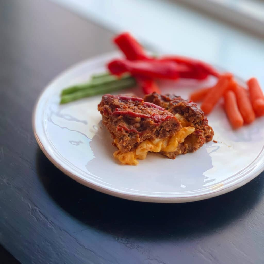 finished mac and cheese stuffed meatloaf with red peppers, carrots and green beans in the background on a round white plate