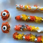 Pretzel rods dipped in white chocolate and colorful candy pieces