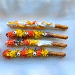 4 pretzel rods covered in melting chocolate, orange and yellow sprinkles and candy eyes