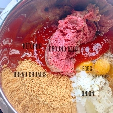 Raw meatloaf ingredients in a mixing bowl with each ingredient labeled