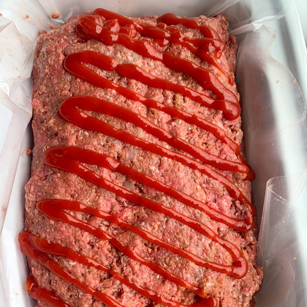 meatloaf stuffed and ready to cooked with a ketchup drizzle on top
