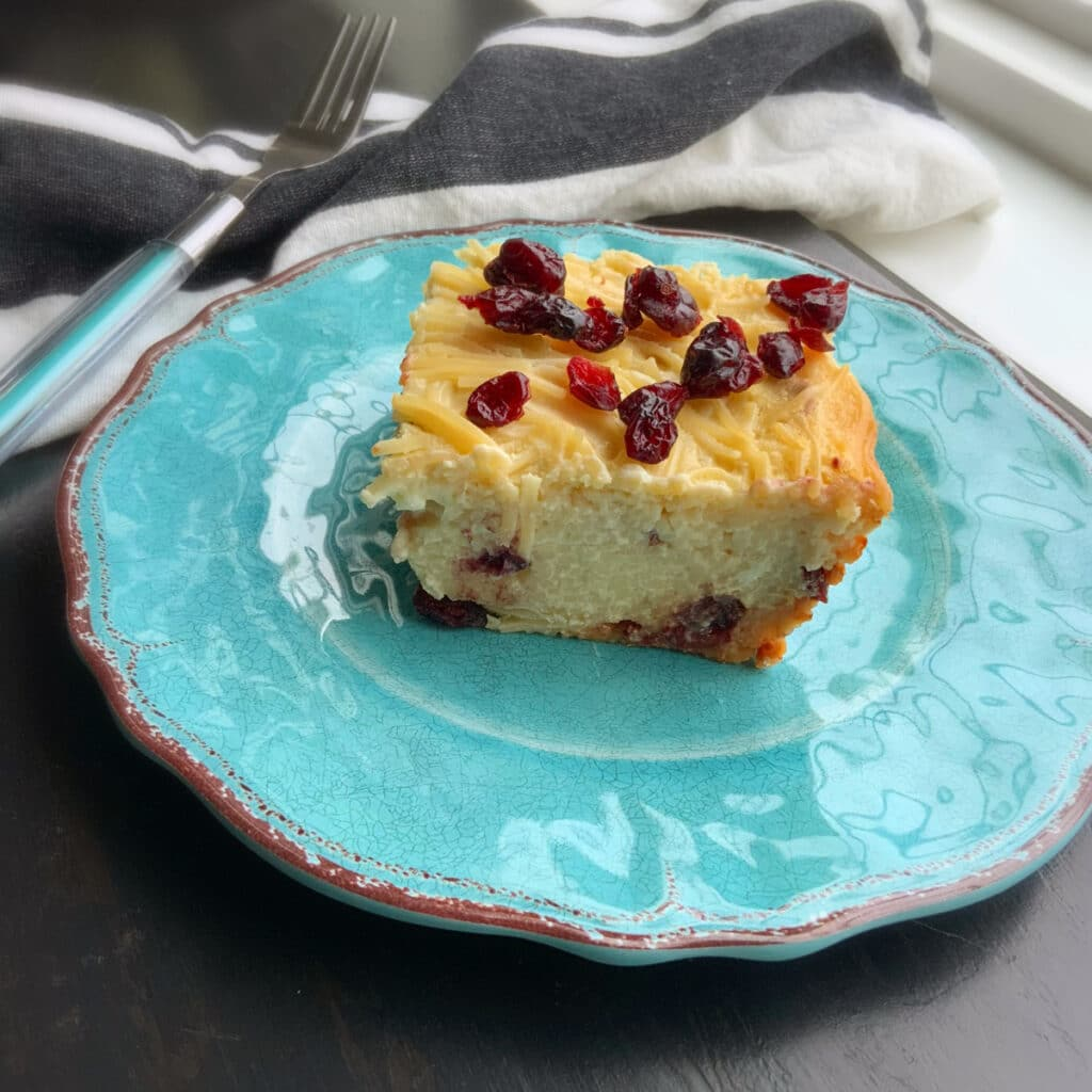 side view of piece of kugel cut from the whole on a turquoise plate with a fork in the background