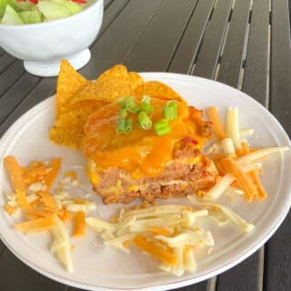 mexican lasagna on a round white plate with shredded cheese laying around it and a salad in the background.