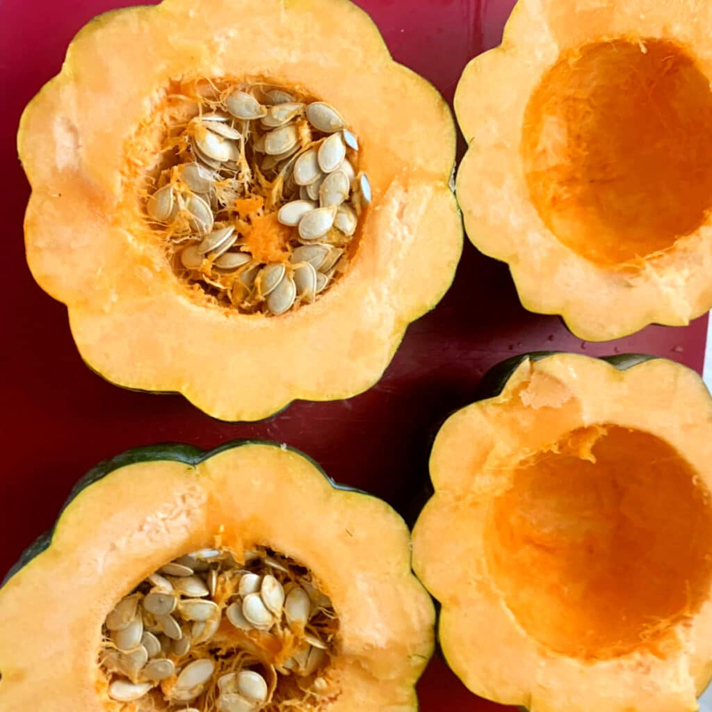 Four halves of acorn squash raw. Two have seeds cleaned out and two don't.