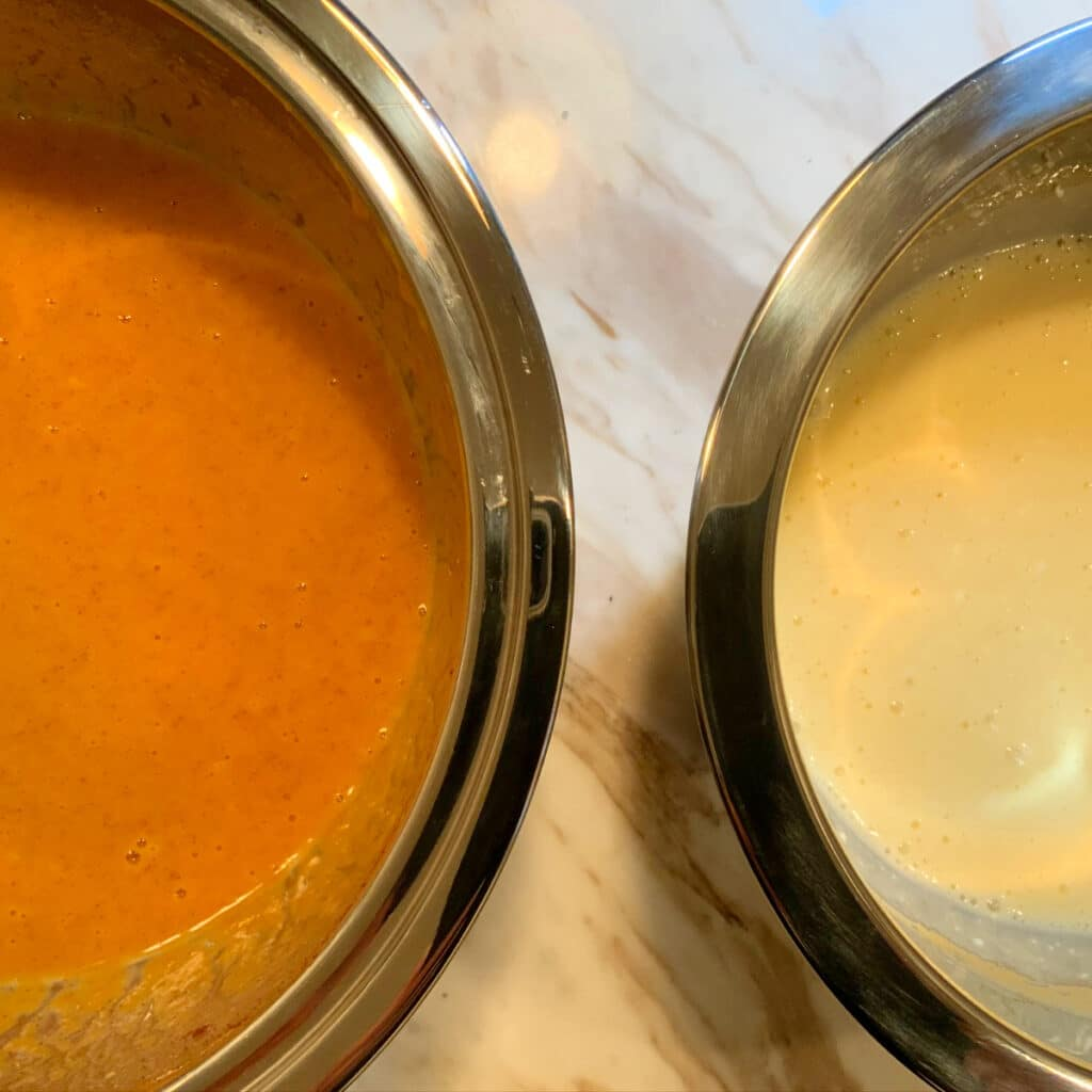 close up of two mixing bowls. one with mixed ingredients for pumpkin layer the other with mixed ingredients of cheesecake layer