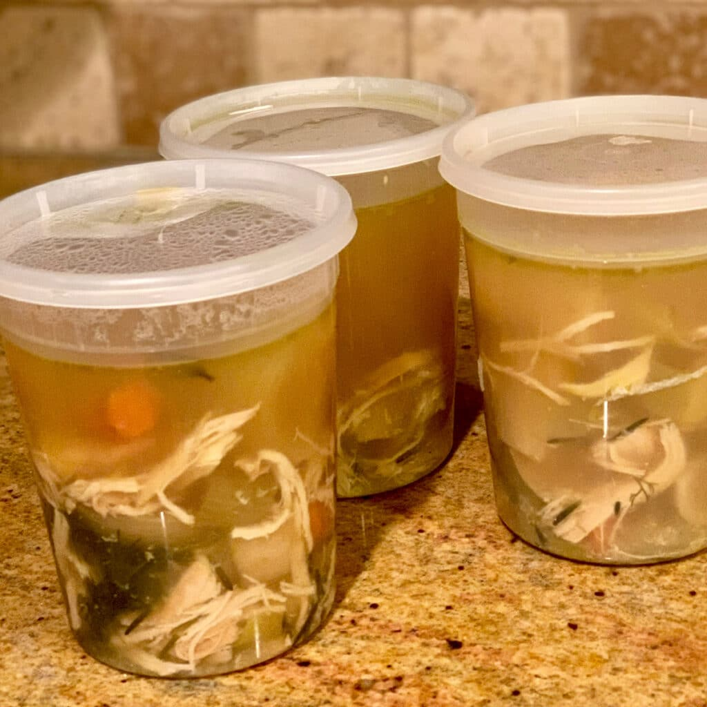 three storage containers with chicken soup ready on a counter top. ready for the freezer