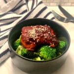 finished thigh on a bed of broccoli in a black round bowl with sesame seeds sprinkled on top