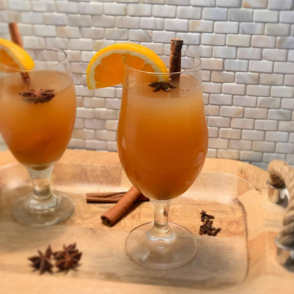 two glasses of hot spiked apple cider in a glass with garnish on a wooden tray with a rope handle