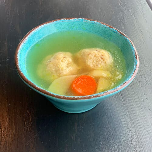 chicken soup in a round turquoise bowl with two matzo balls, carrots and parsnips