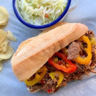 close up of Italian beef on a hoagie roll with red and green pepper rings